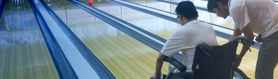 A young man in a wheelchair going bowling.